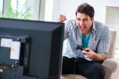 El hombre que juega al juego de ordenador en casa Fotografía de archivo