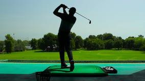 El hombre que juega a golf en la sombra almacen de video