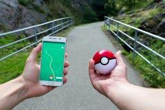 El hombre que juega Pokemon va al aire libre Fotos de archivo libres de regalías