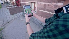 El hombre que juega Pokemon va, dando une vuelta en la ciudad almacen de video