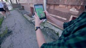 El hombre que juega Pokemon va, dando une vuelta en la ciudad metrajes