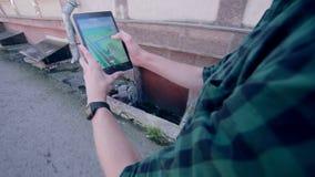 El hombre que juega Pokemon va, dando une vuelta en la ciudad almacen de metraje de vídeo