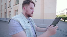 El hombre que juega Pokemon va en la tableta, dando une vuelta en la ciudad metrajes