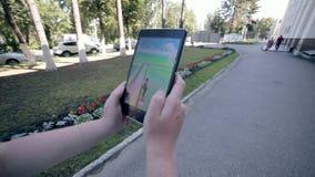 El hombre que juega Pokemon va en la tableta, dando une vuelta en la ciudad almacen de metraje de vídeo