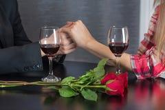 El hombre que lleva a cabo las manos de la muchacha en la tabla del restaurante con dos vidrios de vino tinto y las rosas rojas f fotografía de archivo