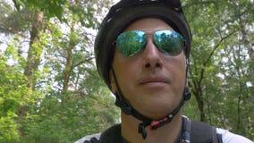 El hombre que lleva las gafas de sol verdes del espejo del aviador monta la bicicleta metrajes