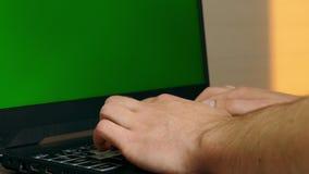 El hombre que mecanografía rápidamente en el teclado del ordenador portátil con greenscreen metrajes
