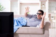 El hombre que mira 3d TV en casa imagen de archivo