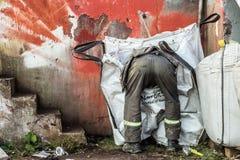 El hombre que mira a través de desperdicios Imagenes de archivo