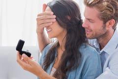 El hombre que oculta sus wifes observa para ofrecerle un anillo de compromiso Imagen de archivo