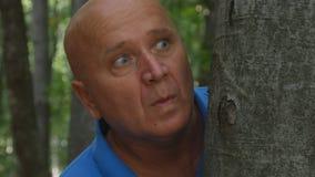 El hombre que parece asustado con los ojos aterrorizados está ocultando después de un árbol en el bosque imagen de archivo