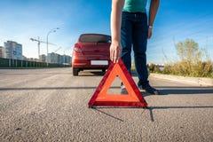El hombre que pone el triángulo rojo canta en el camino después de choque de coche Imágenes de archivo libres de regalías