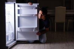 El hombre que rompe dieta en la noche cerca del refrigerador imagen de archivo libre de regalías