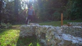 El hombre que salta alrededor de las ruinas del castillo
