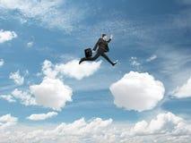 El hombre que salta de la nube imagen de archivo
