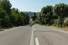 El hombre que salta en el camino vacío globetrotter foto de archivo libre de regalías