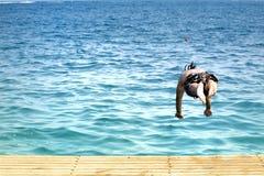 El hombre que salta en el mar Fotos de archivo libres de regalías