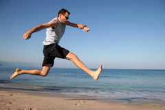 El hombre que salta en la playa Imagen de archivo