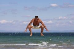 El hombre que salta en la playa. Fotografía de archivo