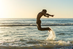 El hombre que salta en la playa en la puesta del sol Imagenes de archivo