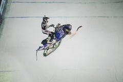 El hombre que salta en moto de nieve en el aire Imagen de archivo