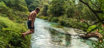 El hombre que salta en ojo azul imagen de archivo