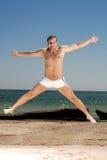 El hombre que salta en una playa Imagen de archivo libre de regalías
