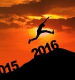 El hombre que salta sobre el número 2016 en la colina Imagen de archivo