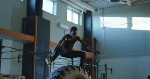 El hombre que salta sobre el neumático grande durante el entrenamiento almacen de metraje de vídeo