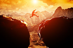 El hombre que salta sobre precipicio entre dos montañas Imagenes de archivo