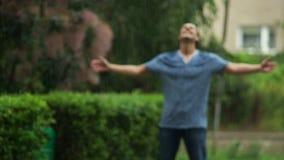 El hombre que se coloca con para arriba aumentadas las manos y los ojos cerrados está gozando de la lluvia caliente del verano al metrajes