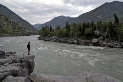 El hombre que se colocaba en una roca grande se separó los brazos sobre el río de la montaña Imágenes de archivo libres de regalías