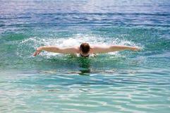 El hombre que se divierte joven nada en el estilo del delfín del mar. Imagenes de archivo