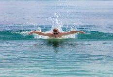 El hombre que se divierte joven nada en el estilo del delfín del mar. Retrato en un día soleado Fotografía de archivo