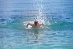 El hombre que se divierte joven nada en el estilo del movimiento de mariposa del mar en un día soleado Imagen de archivo