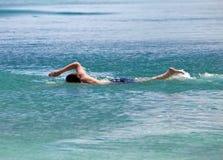 El hombre que se divierte joven nada en el mar Imagenes de archivo