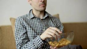 El hombre que se sienta en el sofá y come los bocados del maíz metrajes