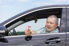 El hombre que se sienta en un coche ofrece el helado Foto de archivo libre de regalías
