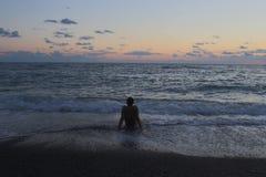 El hombre que se sienta por el mar en la puesta del sol Imagen de archivo