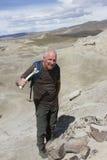 El hombre que sostiene el hueso con el dinosaurio permanece Imagenes de archivo