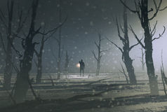 El hombre que sostiene la linterna se coloca en bosque oscuro con niebla Imagenes de archivo