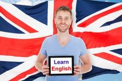 El hombre que sostiene la tableta de Digitaces con aprende el texto inglés Foto de archivo