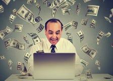 El hombre que usa el ordenador portátil que construye el negocio en línea que hace billetes de dólar del dinero cobra caer abajo  imágenes de archivo libres de regalías