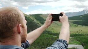 El hombre que usa el teléfono elegante toma un Mountain View de la foto almacen de video
