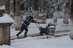 El hombre que usaba una máquina para hilar y torcer de la nieve en un día de invierno después de una nevada descargó 8 pulgadas d Fotos de archivo libres de regalías