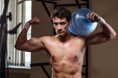 El hombre rasgado muscular con la botella de agua grande foto de archivo