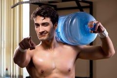 El hombre rasgado muscular con la botella de agua grande foto de archivo libre de regalías