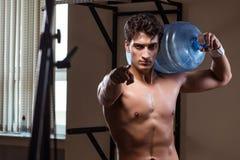 El hombre rasgado muscular con la botella de agua grande fotografía de archivo libre de regalías