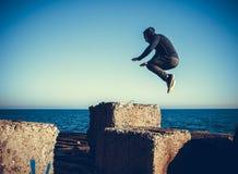 El hombre realiza salto freerunning en piedras Fotos de archivo libres de regalías