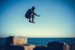 El hombre realiza salto freerunning en piedras Imágenes de archivo libres de regalías